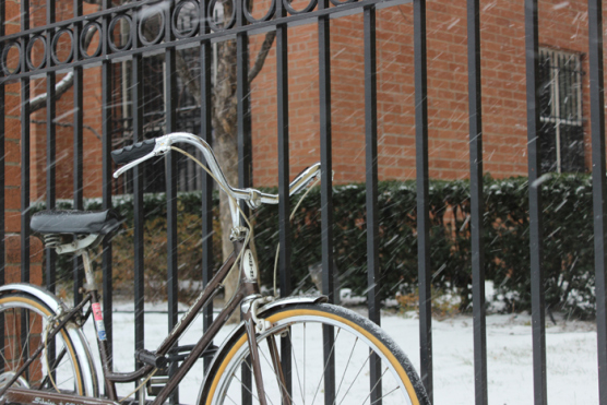 bike next to a fence in the snow