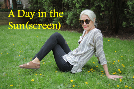 A day in the Sunscreen, Behind the Mirror, Amanda Teague, Sunscreen tips, girl with white hair laying in the grass with some flowers and relaxing in a black and white elizabeth and James tunic and ripped black current elliott jeans with birkenstocks