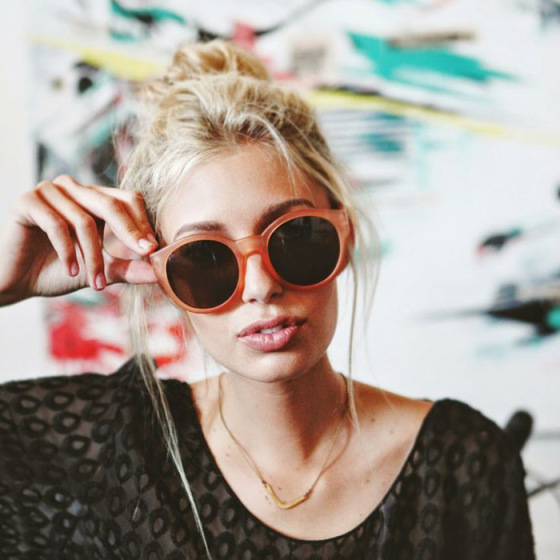 blonde girl with huge sunglasses holding her hand to her head