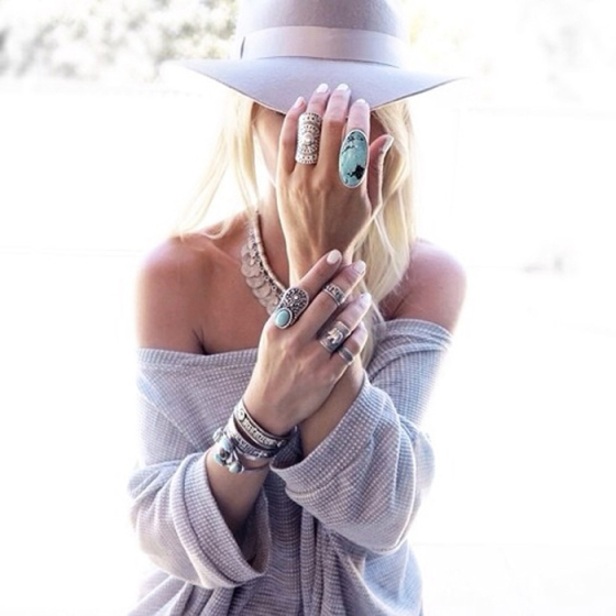 blonde girl in a beige fedora hat and beige sweater holding the hat with her hand wearing rings of turquoise and gold