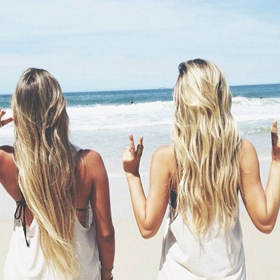 two girls at the beach one with blonde hair and the other with brown hair walking towards the ocean with their backs to the photo holding a peace sign