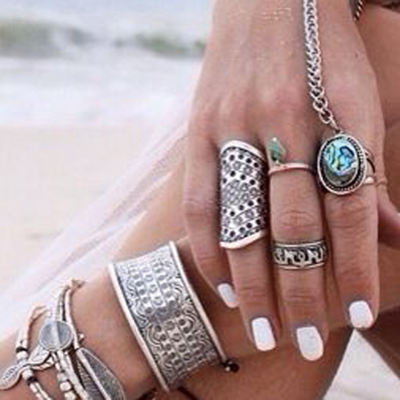 hand on leg at the beach in the sand with a lot of rings on and many bracelets with light almost white nail polish