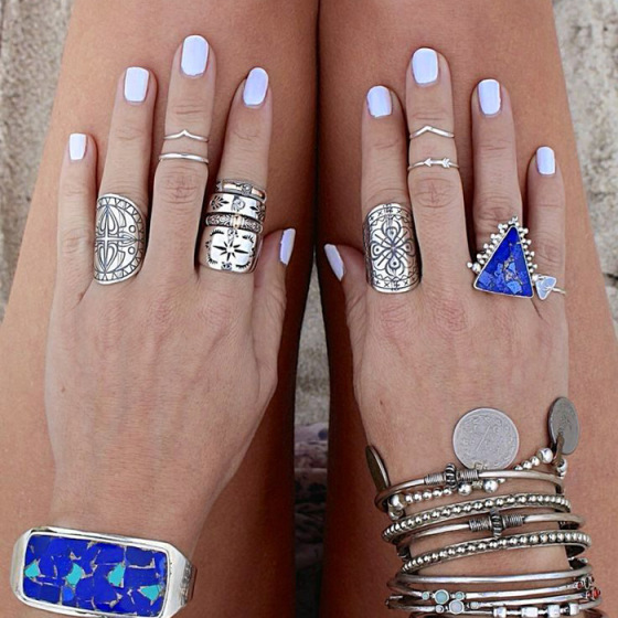 two hands on two legs with light blue nail polish and lots of jewelry with blue