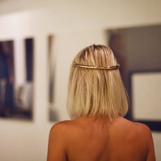 long blonde bob pulled back with gold twist in an art gallery