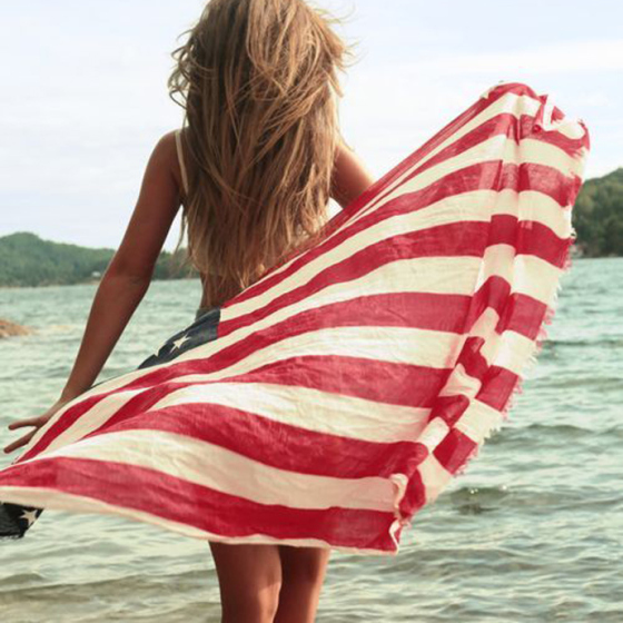 Happy 4th of July, Behind the Mirror, pretty girl with blonde hair walking out to the ocean with an american flag blowing in the ocean breeze