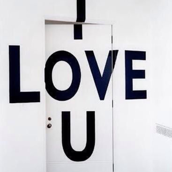 I love you written on a wall with door with black paint, behind the mirror, like your face
