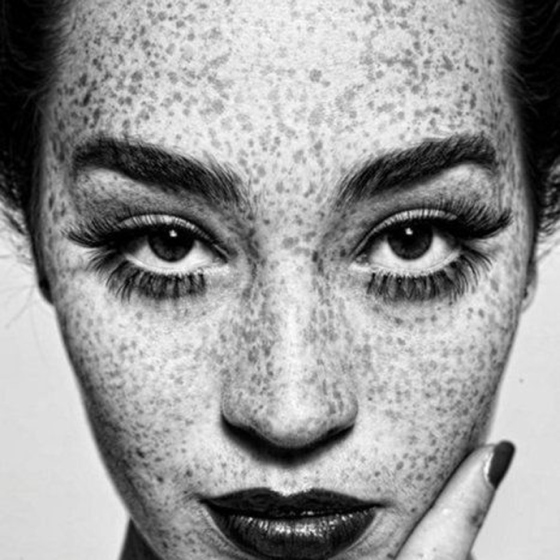 black and white photo of girl with freckles, behind the mirror, like your face