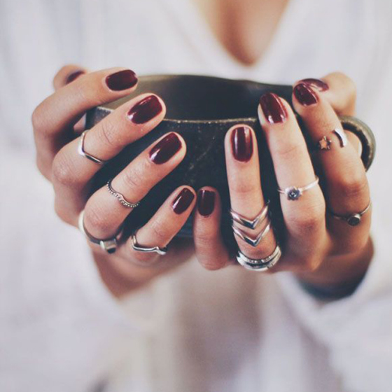 cup of coffee held by hands with dark wine nails polish and lots of rings, behind the mirror, like your face